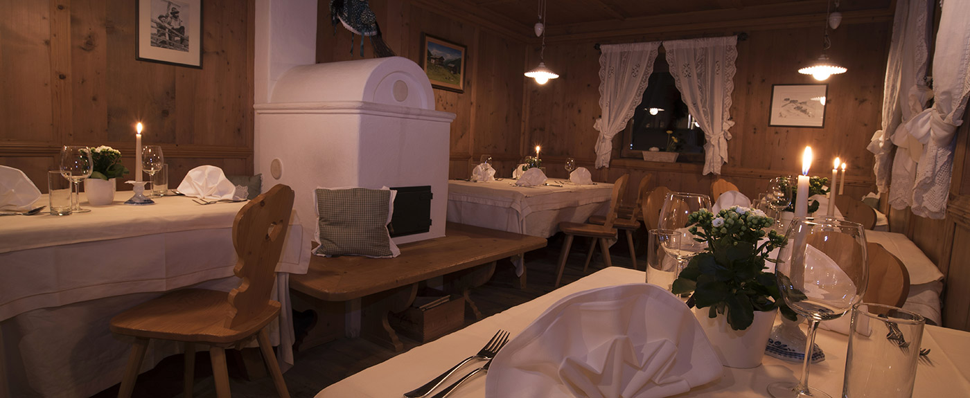 The stube at Hotel Arnstein with tiled stove and tables by candlelight