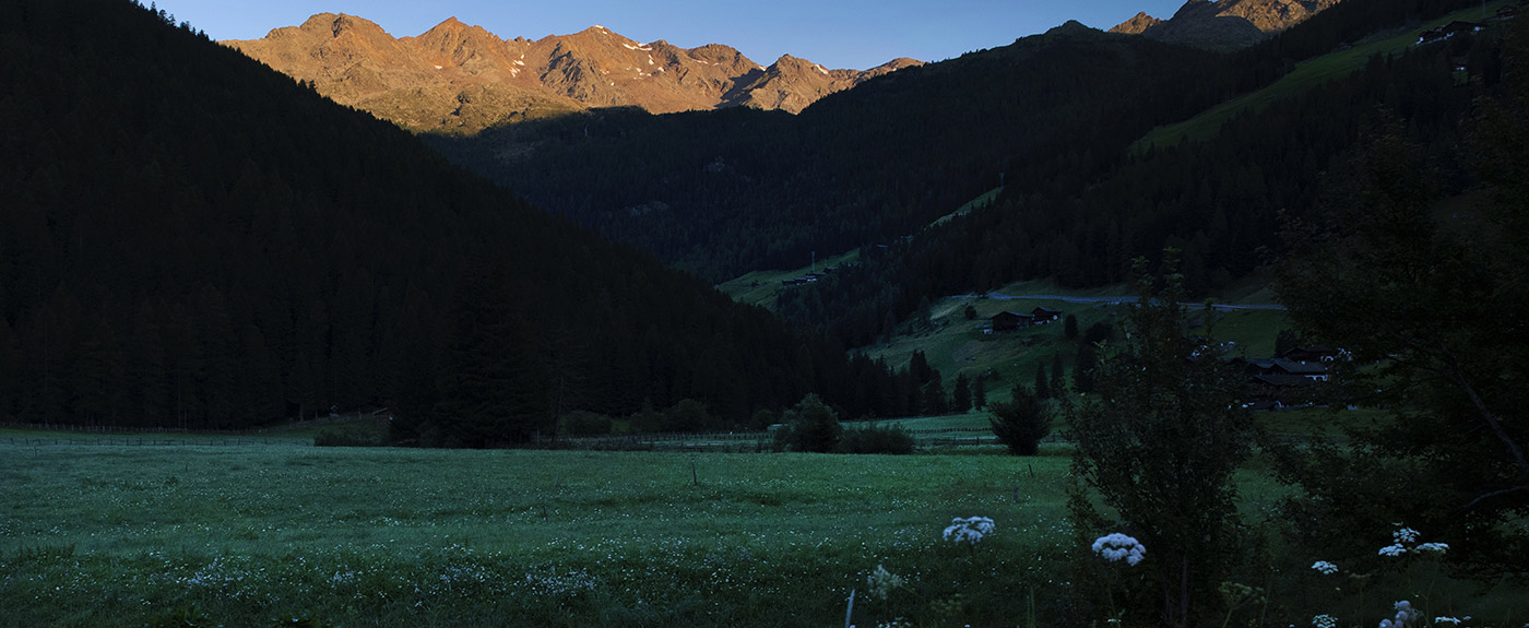 Shadowy meadow with sunlit mountain tops at the back