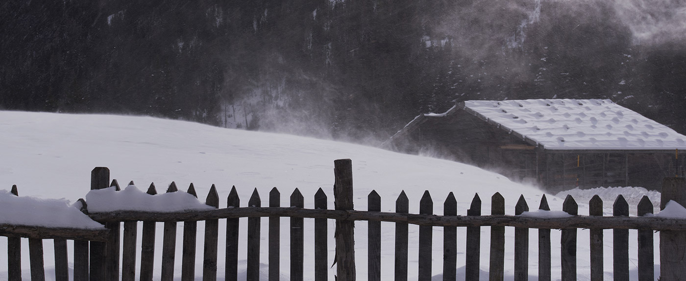 Wooden fence and hut amid the snowy landscape